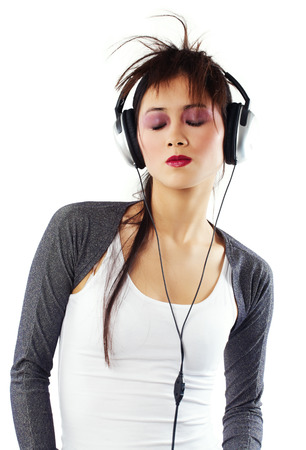 stereo cut: Young Asian woman with headphones posing on white background.