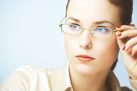 wearing glasses: Portraits of young woman wearing glasses and silk blouse photographed on blue background.