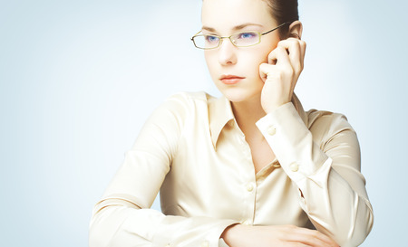 woman wearing glasses: Portraits of young woman wearing glasses and silk blouse photographed on blue background.