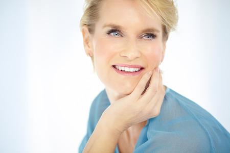 blusa: Hermosos sonrientes en interiores mujer elegante vistiendo blusa azul y el pelo corto y rubio.