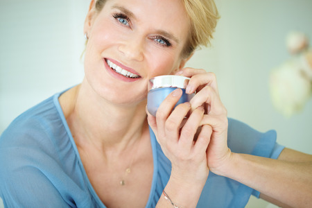 Beautiful smiling elegant woman indoors wearing blue blouse and short blond hair holding a cream jar. Skincare concept over forty.