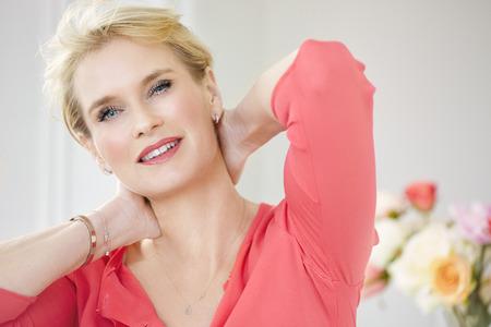 blonde yeux bleus: Beau sourire intérieur de femme élégante portant un chemisier rose et cheveux blonds courts.