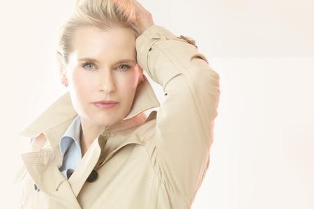 Beautiful modern elegant woman indoors wearing trench coat in studio.