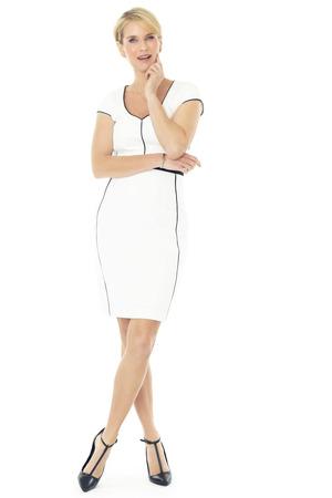 Mooie glimlachende elegante vrouw binnen, gekleed in witte jurk en zwarte pumps op een witte achtergrond.