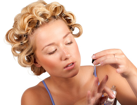 hair curlers: Cheerful girl wearing hair curlers and grooming her nails.