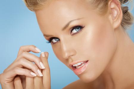 rubia ojos azules: Primer plano de un modelo con maicure francés. Foto de archivo