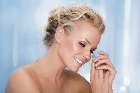 rubia ojos azules: Modelo feliz que presenta en el fondo azul.