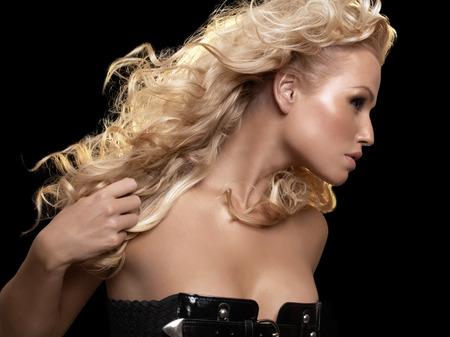 cabello rubio: Mujer con el pelo largo y rubio sobre fondo negro.