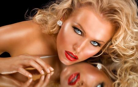 cabello rubio: Modelo hermoso con el pelo largo y rubio que pone en un espejo.