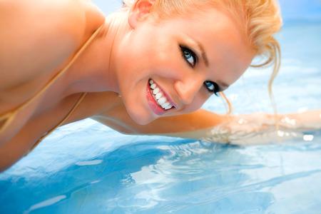 rubia ojos azules: Mujer feliz que pone en el agua azul brillante.