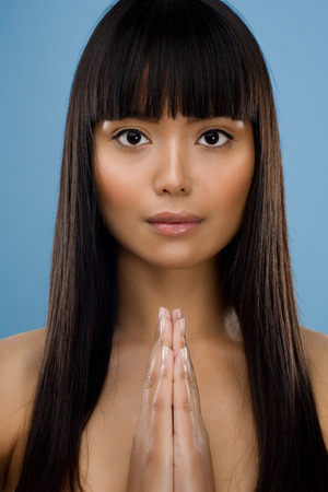 Asian woman with hands together as praying.