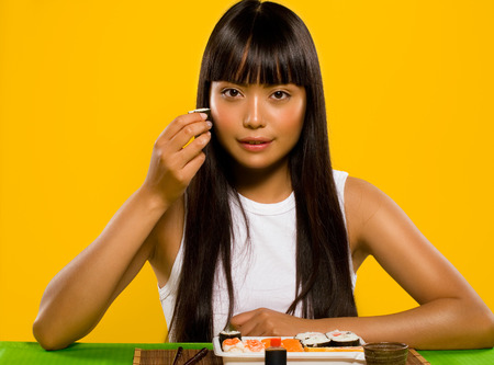 asian model: Asian model eating sushi.