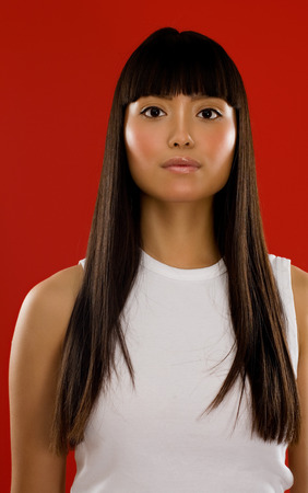 model posing: Young Asian model posing on red background. Stock Photo
