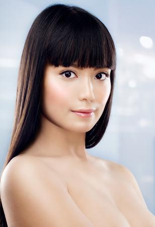 long shot: Asian model posing on light blue background.