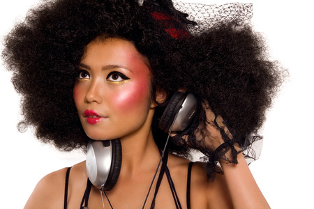 asian afro: Girl dressed in modern funky Japanese style with headphones. Stock Photo