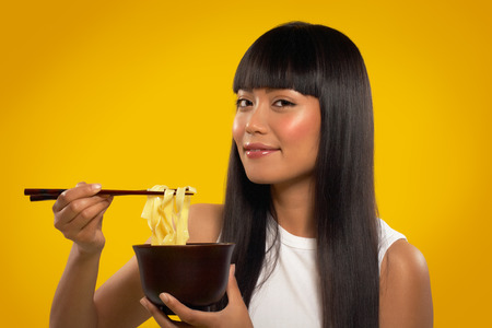 Cheerful Asian girl with noodles and chopsticks.