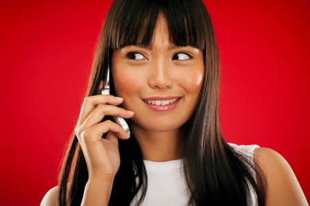 Young Asian girl with mobile phone on red background. Stock Photo