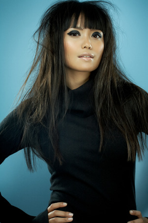 messy hair: Asian fashion model with long messy hair wearing black knitwear. Stock Photo