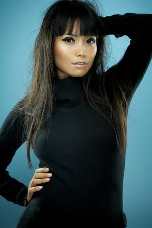 black hair blue eyes: Asian fashion model with long messy hair wearing black knitwear. Stock Photo