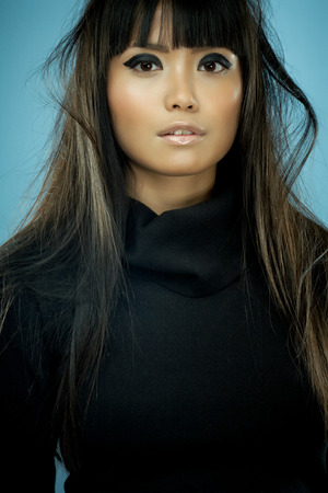 hair black color: Asian fashion model with long messy hair wearing black knitwear. Stock Photo