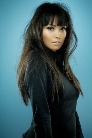 Asian fashion model with long messy hair wearing black knitwear. Banco de Imagens