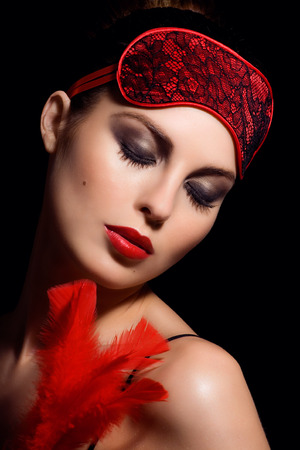 blindfold: Beautiful woman with ref feather, red lipstick and red blindfold.