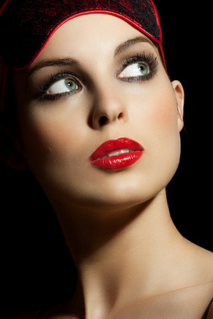 Beautiful woman with red lipstick and red blindfold.