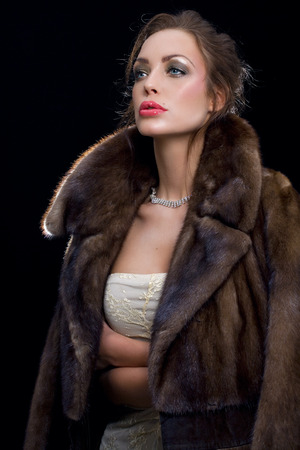 Woman wearing jewelry and mink coat.