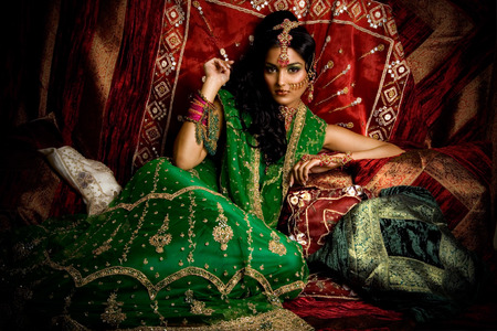 luxe: Indian woman laying in luxe ethnic interior.