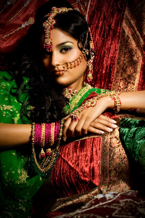 Indian woman laying in luxe ethnic interior.