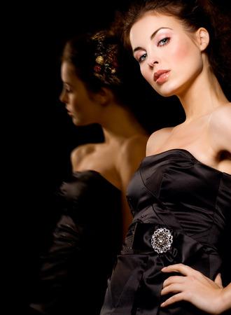 lbd: Fashion model standing next to mirror. Stock Photo