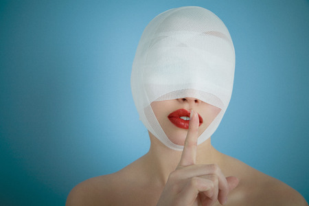 plastics: Woman after plastic surgery with secrecy expression. Stock Photo