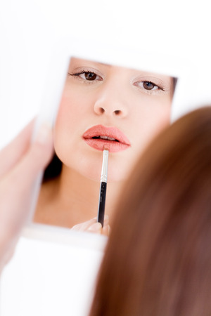 applying lipstick: Model applying lipstick. Stock Photo