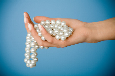 Female hand holding string of fake pearls.