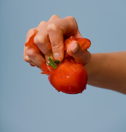 Female hand squeezing a tomato.