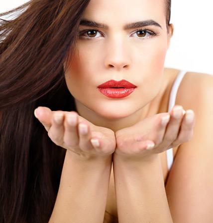 capelli castani: Bella donna con lunghi capelli castani che soffia baci. Archivio Fotografico