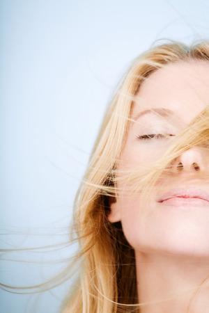 blonde yeux bleus: Femme wit yeux fermés sous le vent. Banque d'images