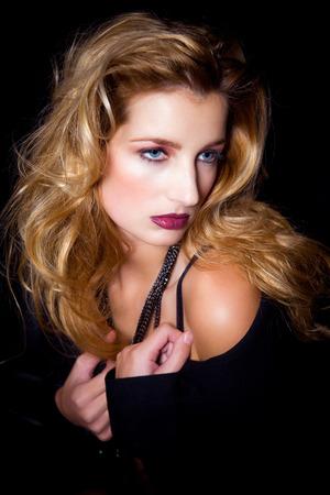 cheveux blonds: Femme woth de longs cheveux blonds sur fond noir.