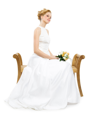 wooden bench: oung bride sitting on wooden bench with flowers.