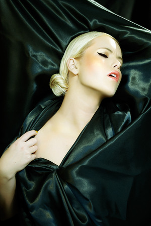 dramatically: Woman wrapped in satin posing dramatically.