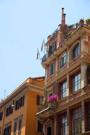 fasade: Colorful buildings on street of Rome against blue sky.
