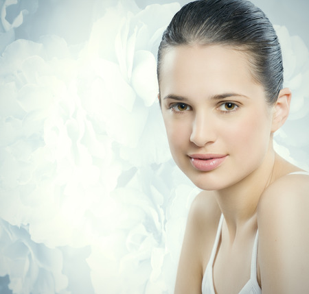smooth skin: Beautiful young European woman with fresh smooth glowing skin. Delicated blue roses background. Stock Photo