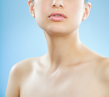Mooie jonge Europese vrouw met verse gladde gloeiende huid en volle lipst over blauwe achtergrond.