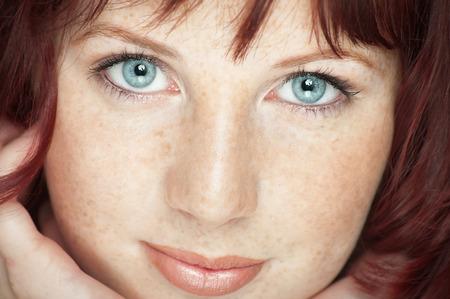 とび色の髪、青い目、そばかすポーズを青い背景の上に新鮮な美少女