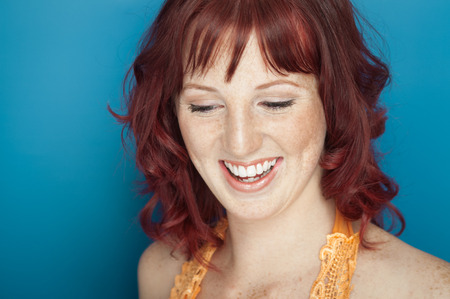 freckles: Beautiful fresh girl with auburn hair, blue eyes and freckles posing over blue background.