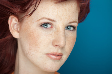 Bella fresca ragazza con i capelli ramati, occhi azzurri e lentiggini posa su sfondo blu.
