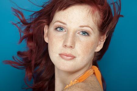 auburn hair: Beautiful fresh girl with auburn hair, blue eyes and freckles posing over blue background.