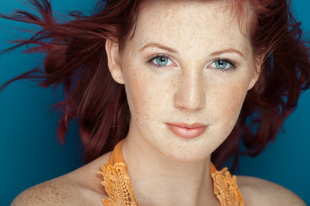 Beautiful fresh girl with auburn hair, blue eyes and freckles posing over blue background.