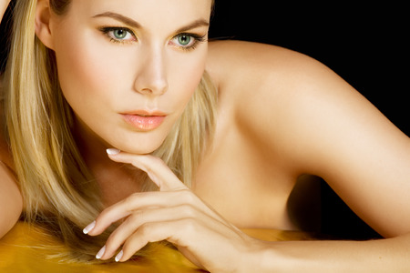 medium length: Beautiful blonde woman resting on golden sheet.