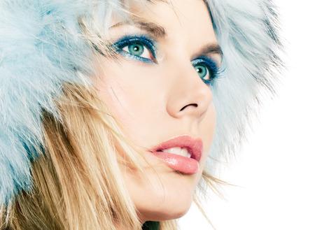 blonde yeux bleus: Gros plan du visage de femme en chapeau de fourrure. Banque d'images